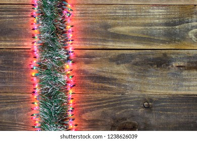 Blank antique rustic wood Christmas sign with garland and colorful string of lights  border; holiday background with copy space