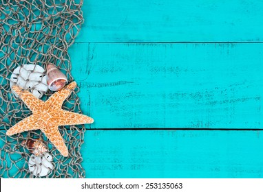 Blank antique teal blue aged wooden sign background with fish net border, sand dollars, seashells and one gold starfish; beach background with painted copy space