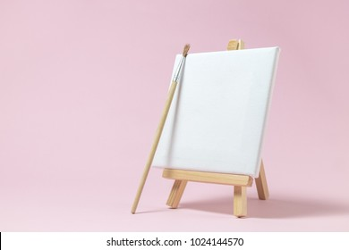 Blank art canvas on easel and paintbrush against pastel pink rose background. Artist minimal concept. Space for copy.