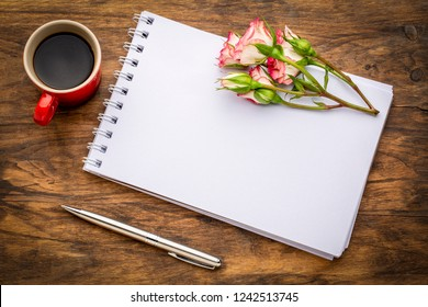 blank art sketchbook with flowers and coffee on a grunge wooden table
