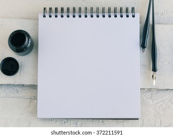 Blank artist sketchbook on white wooden background with calligraphy pens and ink. View from the top. Open blank sketchbook. Artistic mockup template for your design.