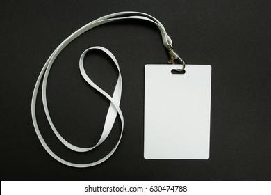 Blank badge mockup isolated on black. Plain empty name tag mock up hanging on neck with string, on white background.
