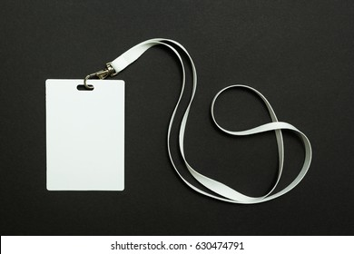 Blank badge mockup isolated on black. Plain empty name tag mock up hanging on neck with string