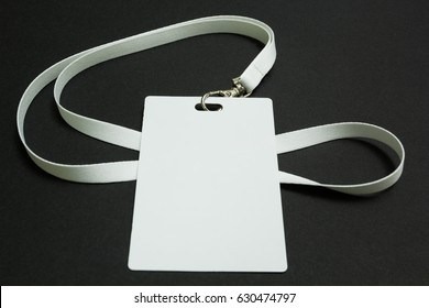 Blank badge mockup isolated on black. Plain empty name tag mock up hanging on neck with string.