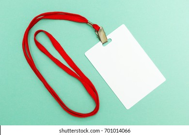 Blank badge mockup isolated on green. Plain empty name tag with red string.