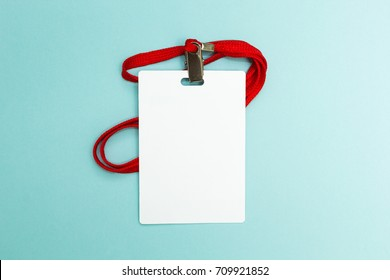 Blank badge mockup isolated on blue background. Plain empty name tag mock up with red string.