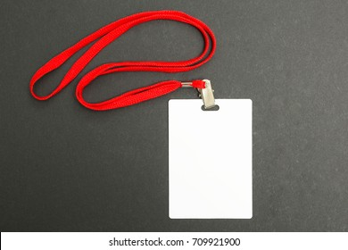 Blank badge mockup isolated on black. Plain empty name tag mock up with red string.
