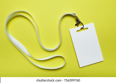 Blank badge mockup isolated on yellow. Plain empty name tag with string.