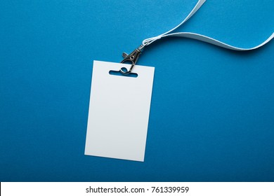 Blank badge mockup isolated on blue background. Name Tag with ribbon.