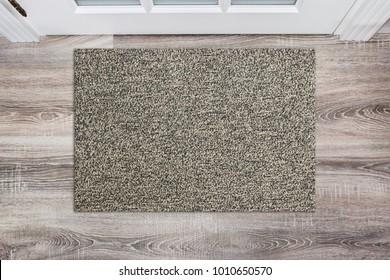 Blank beige woolen doormat before the white door in the hall. Mat on wooden floor, product Mockup
