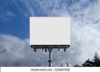 Blank billboard for advertising, against blue sky