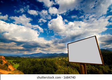 Blank billboard agains a nive blue sky with clouds