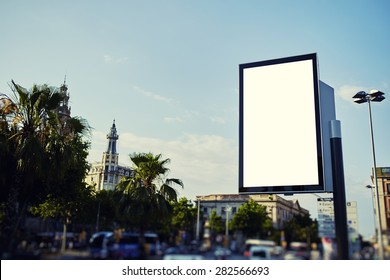 Blank billboard with copy space for your text message or content, public information board in the big town, advertising mock up empty banner in metropolitan city at beautiful sunny day, blur effect