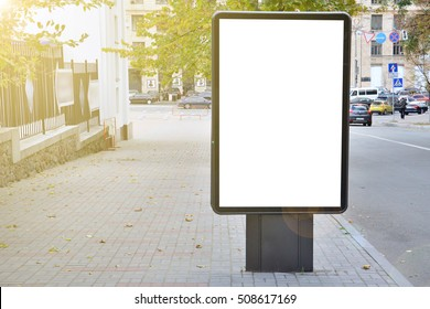 Blank billboard with copy space for your text message or content, outdoors advertising mock up, public information board on city road, flare sun light. Empty Lightbox on urban setting sidelines