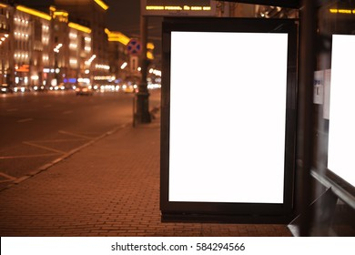 Blank billboard with copy space for your text message or content, public information board on roadside, advertising mock up empty banner on a bus stop. a reflection of the billboard in the side window