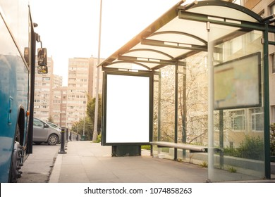 Blank billboard at a frequent bus station in downtown of Istanbul. A station with a bench and glass roof near to road captured at sunset and rush hours without people.