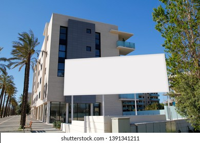 Blank billboard in front of new buildings for sale