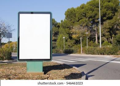 Blank billboard in a green street with trees