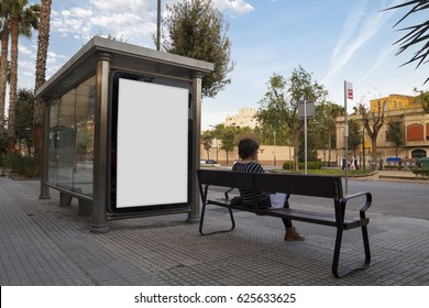 Blank billboard mock up in a bus stop, with a young woman sitting in a bench
