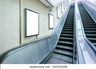 Blank billboard mock up on the wall beside the escalator at the subway station. Advertising concept