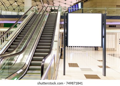 Blank billboard near escalator in department store