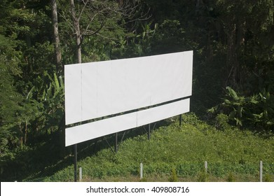 Blank billboard for new advertisement, with green trees