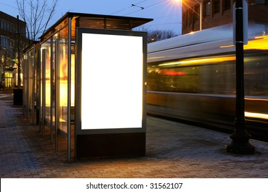 Blank billboard on bus stop shelter at night