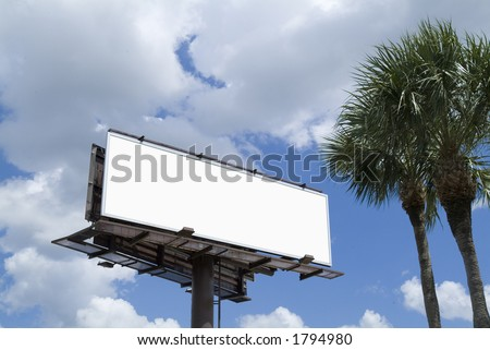 Blank billboard with palm trees in blue sky with clouds