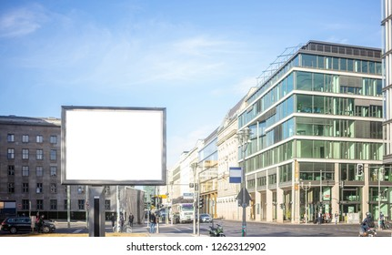 Blank billboard for public advertisement on the roadside. Space for text on the white board. People and city background.