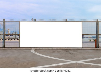 A blank billboard ready for new advertising on the harbor fence, big copy space