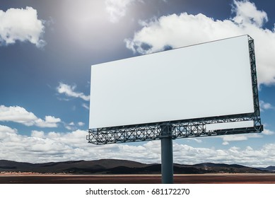 Blank billboard sign in the blue sky above the mountains