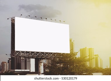 Blank billboard with sky and buildings in a city at background - vintage style