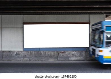 blank billboard in street with bus passing by