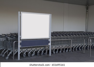Blank billboard in a supermarket, next to shopping carts