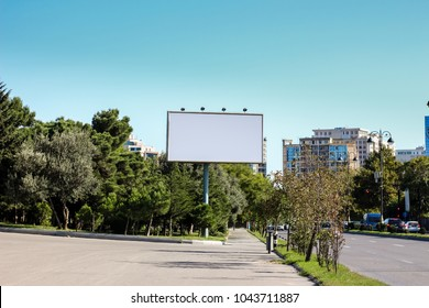 Blank billboard for your new advertisement beside street and trees.