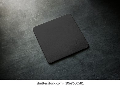 Blank black beer coaster mockup lying on grey desk. Square clear dark bar cork table-mat design mock up top side view. Quadrate cup or bottle rug display, isolated.