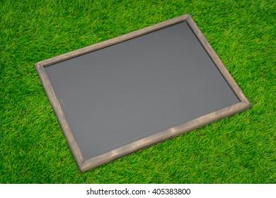 Blank black board on grass field