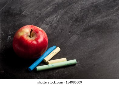 blank black chalkboard with chalk and apple