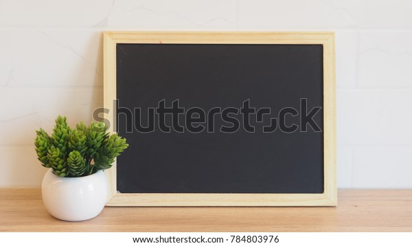 Blank black chalkboard on wood panel table and and white bricks wall.