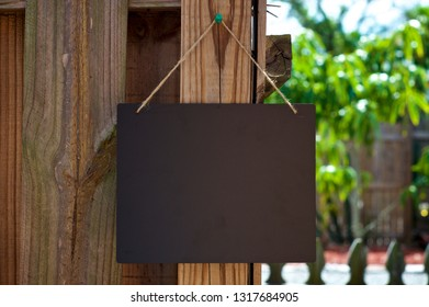 A Blank black chalkboard sign hanging from jute rope outdoors on old wooden fence.