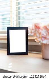 Blank black color picture frame template for place image or text inside on the desktop table work space with laptop and flower. window light