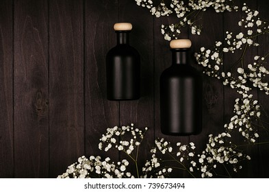Blank black cosmetics bottles with white small flowers on dark wood board, mock up, top view. Template for advertising, designers, branding identity, cover.