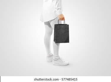 Blank black craft paper bag design mockup holding hand, clipping path. Woman hold kraft textured purchase pack mock up. Clear shop bagful branding template. Shopping carry package in persons arm.