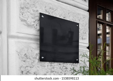 Blank black glass signplate on textured wall mockup. Empty lawyer square nameplate mock up. Clear glassy banner for shop or office entry mokcup template.