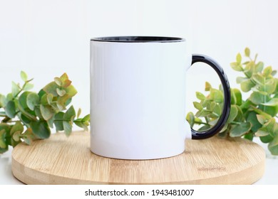 Blank black handle mug mockup photo with eucalyptus ,black rim mug on wood table