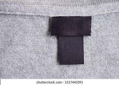 Blank black laundry care clothing label on fabric texture