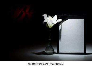 Blank black mourning farme with white lily flower in vase.on dark background with red decoration
