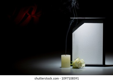 Blank black mourning frame, with smoky candle and white rose, on dark background with red decoration