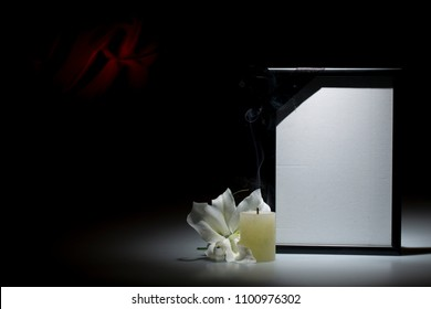 Blank black mourning frame, with smoky candle and white lily flower on dark background with red decoration