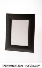 blank black mourning picture frame on bright background for obituary card